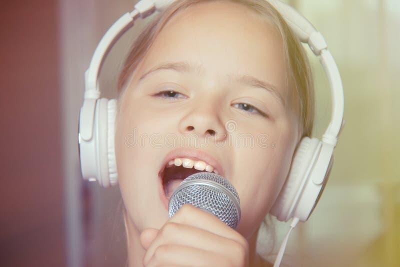 Close-up van zingend Kaukasisch kindmeisje Het jonge meisje zingt emotioneel in de microfoon, houdend het met hand stock afbeelding