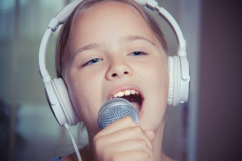 Close-up van zingend Kaukasisch kindmeisje Het jonge meisje zingt emotioneel in de microfoon, houdend het met hand royalty-vrije stock afbeelding