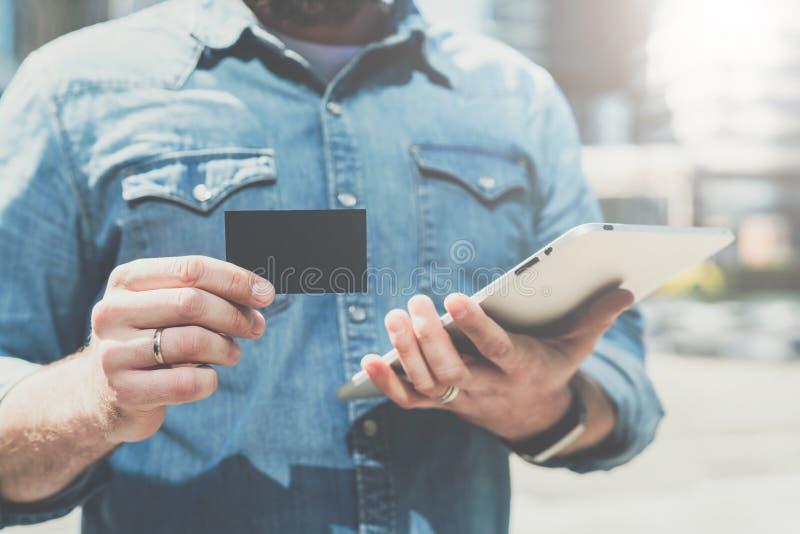 Close-up van zwart leeg krediet, zaken, het roepen, visitekaartje in hand van jonge zakenman, die zich in openlucht bevinden stock afbeelding
