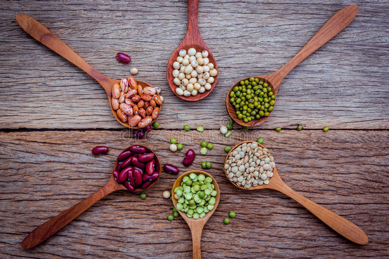 Close up of various beans in wooden spoons setup on wooden background. royalty free stock photos