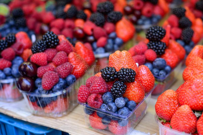 Close-up of various berries strawberries, blackberries, blueberries, red currants, raspberries on the market counter. royalty free stock photo