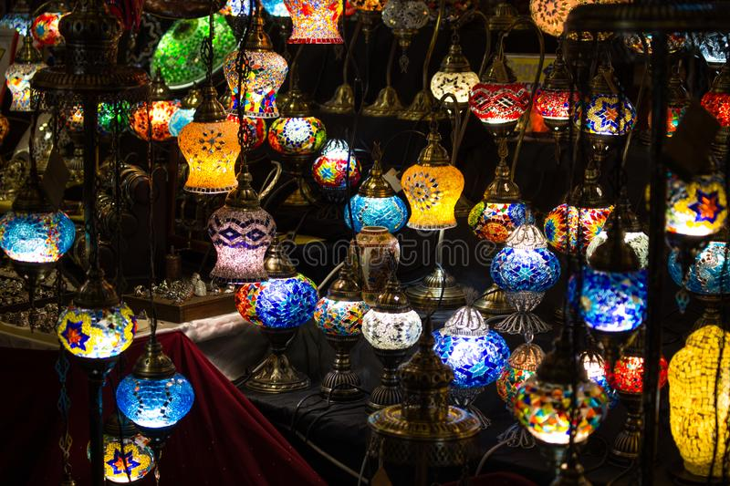 Close-up of various colorful round shaped retro glass lamps in darkness, in the market, as vintage color effect royalty free stock images