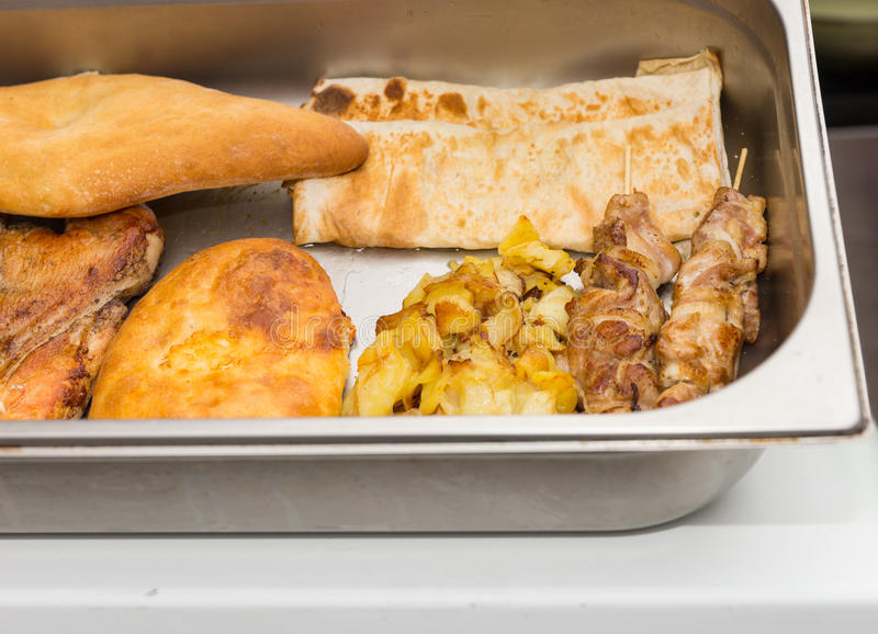 Close up on various meats in serving pan. Close up on various fried and baked meats neatly arranged in single stainless steel serving pan stock image