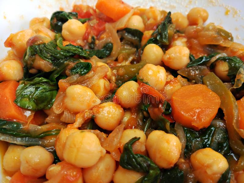 Spinach and chickpea stew on a white plate. Close-up of vegan spanish spinach chickpea stew, fresh and healthy, with herbs and vegetables. Potaje de garbanzos stock photography
