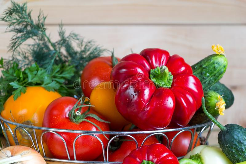 Close up vegetables harvest in wicker basket on wooden background. Red and yellow pepper, tomatoes, onion and green bow stock images
