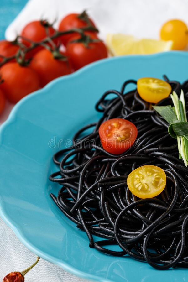 Close up vegetarian black pasta with cuttlefish ink in blue plate with red and yellow cherry tomatoes on light background stock photos