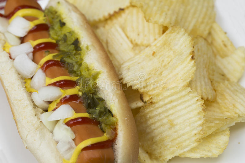 Close Up of Veggie Dog and Chips. Veggie hot dog topped with mustard, ketchup, onions and relish, served with potato crisps (chips stock image