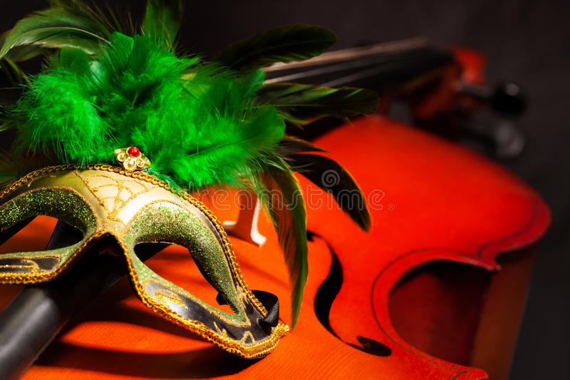 Close-up of Venetian mask with feathers on cello. Close-up of Venetian mask with green feathers on violoncello with the black background royalty free stock images