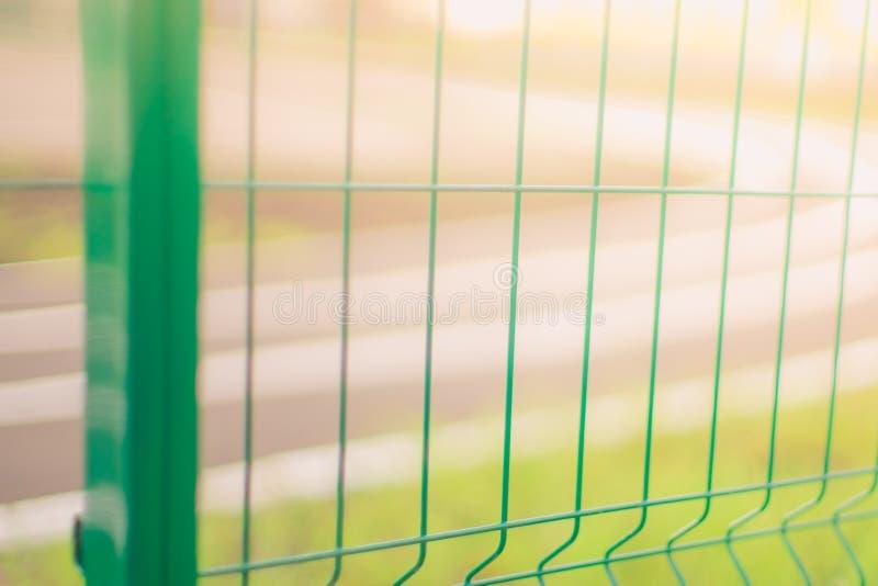 Close up verde da malha da cerca, pista de atletismo do fundo no dia ensolarado morno imagem de stock royalty free