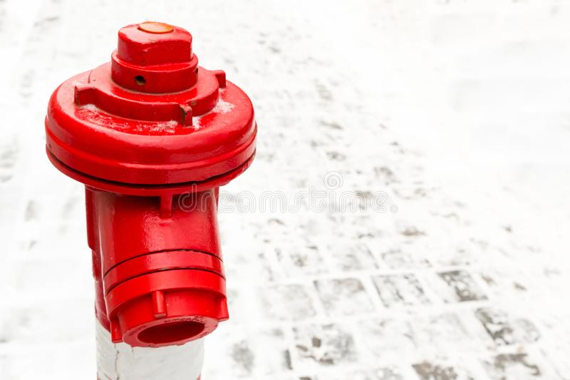 Close-up vermelho da boca de incêndio do fundo industrial que contrasta em um fundo do espaço de pedra da cópia da área da neve imagens de stock royalty free