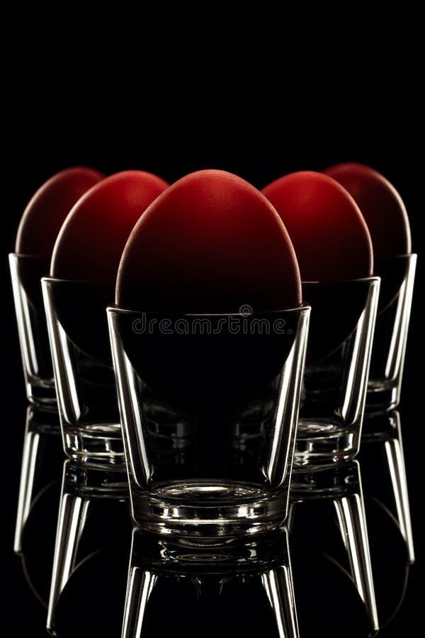 Close-up vermelho dos ovos da páscoa no vidro, pirâmide arranjada no CCB preto fotografia de stock royalty free