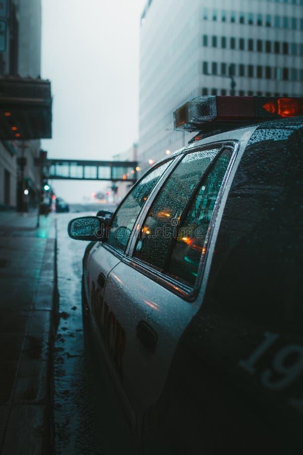 Close up vertical disparado de um carro do polica estacionado em uma estrada chuvosa fotografia de stock royalty free