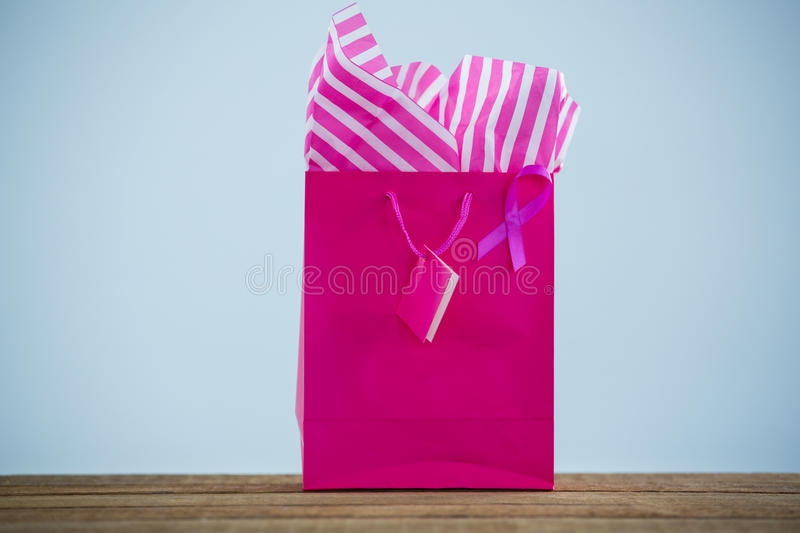 Close-up of vibrant pink Breast Cancer Awareness ribbon on shopping bag over wooden table. Against white background royalty free stock images