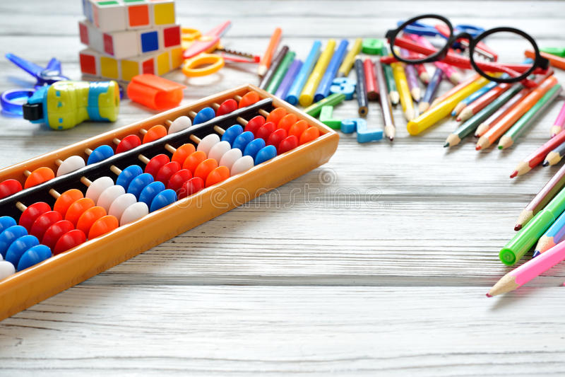 Close up view of abacus scores mental arithmetic with colorful back to school supplies over white table. Space for text. royalty free stock photography