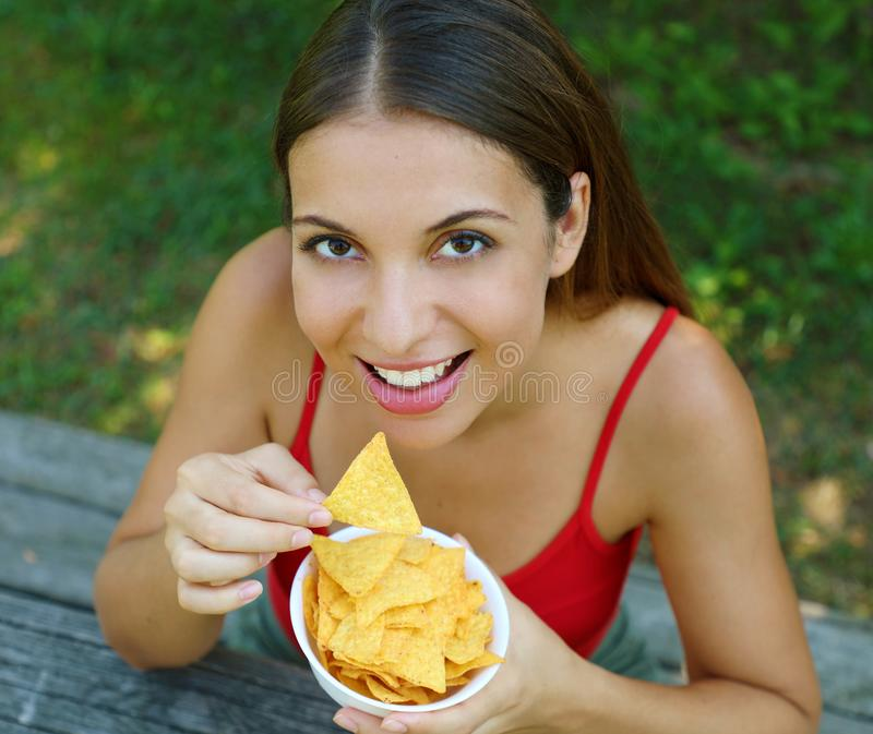 Close up view from above of beautiful young woman eating tortilla chips outdoor royalty free stock image