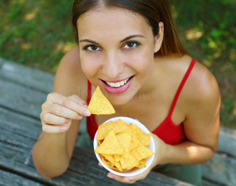 Close up view from above of beautiful young woman eating tortilla chips outdoor royalty free stock photo