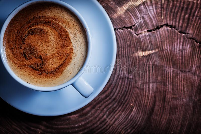 Close up view from above coffee with foam and cinnamon in white ceramic cup on vintage cross section tree trunk stock photos