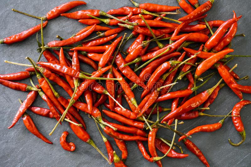 Close-up view from above of a pile of bright red Thai bird chiles on a black slate table stock image