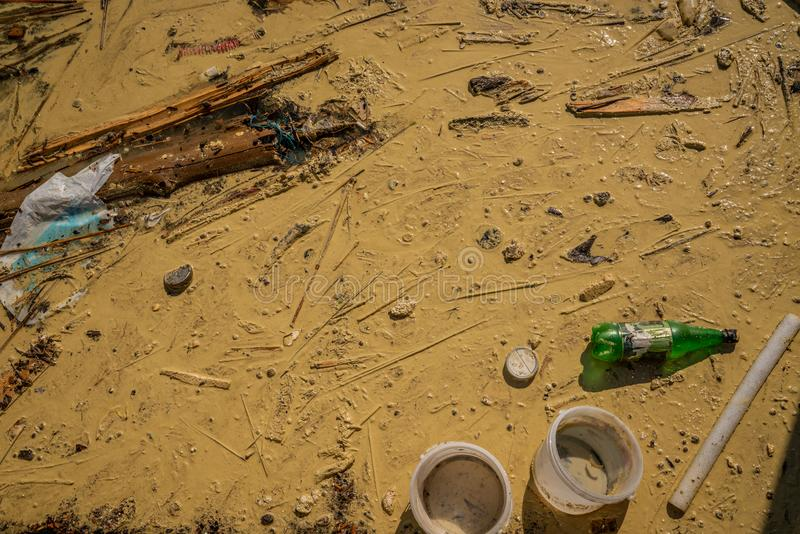 Close up view from above of polluted dirty muddy water with debris, garbage and plastic. royalty free stock photos