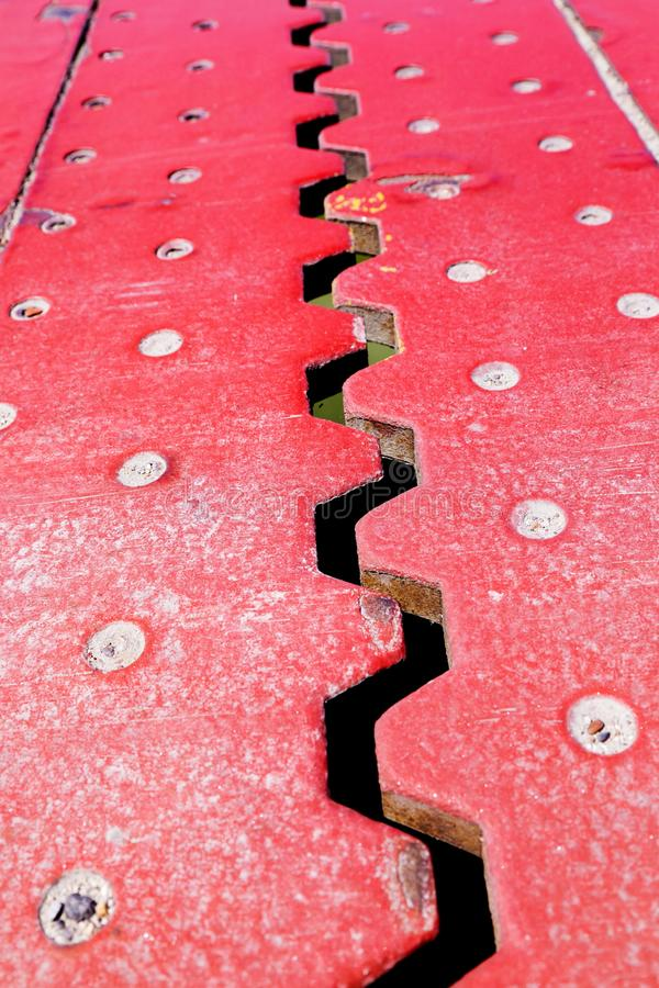 Close up view from above of an red iron dilatation joint placed. On a opening bridge road - Zigzag line from steel royalty free stock photography