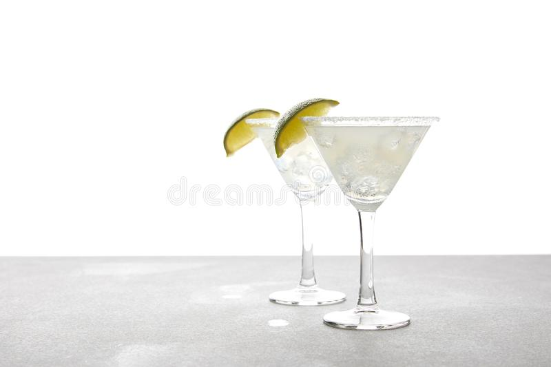 close up view of alcohol margarita cocktails with lime on grey surface on white royalty free stock photo