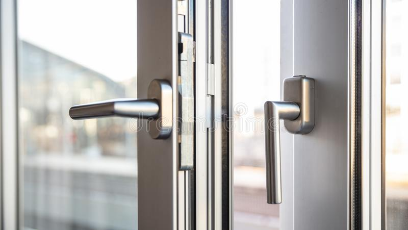 Close up view of aluminum door window handles, against a blurry stock photography