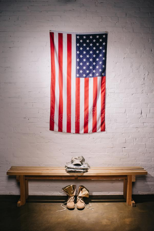 close up view of american flag hanging on white brick wall and arranged military uniform vector illustration