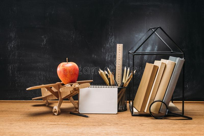 close up view of apple on wooden toy plane notebook books and pencils on tabletop with empty stock photography