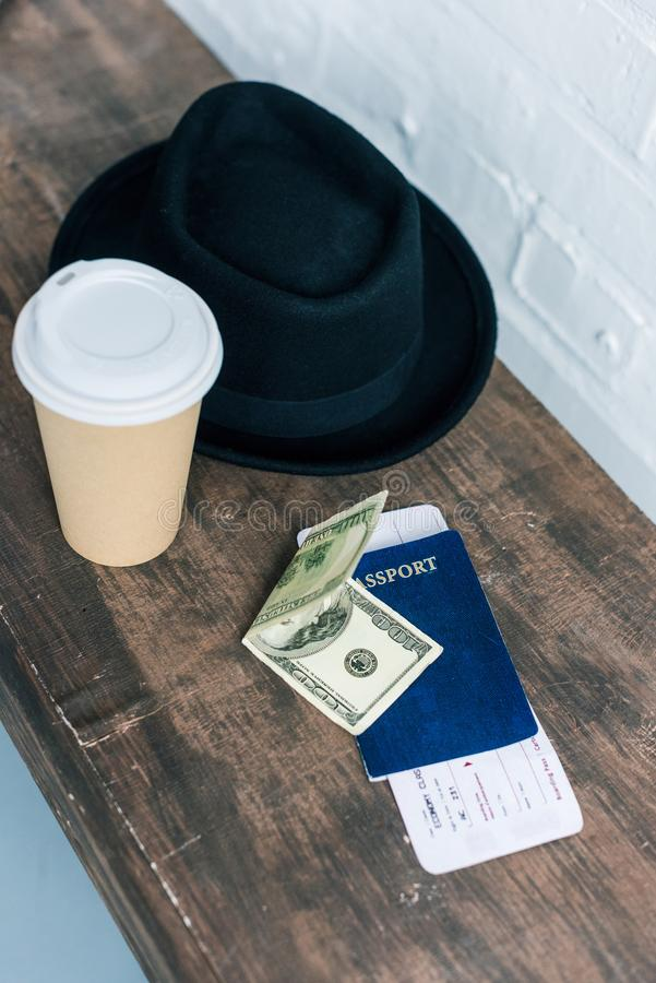 Close up view of arranged passport, cash, coffee to go and hat. On wooden bench stock photos
