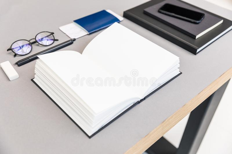 close up view of arranged pile of empty opened notebook, eyeglasses, passport and ticket stock photos