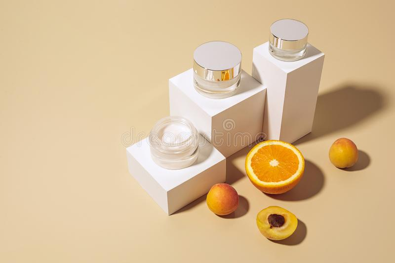 Close up view of arranged skin care creams and fruits. On beige backdrop stock photos