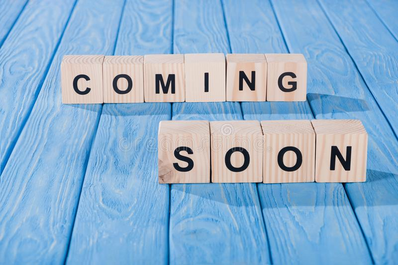 Close up view of arranged wooden blocks into coming soon phrase on blue. Wooden surface stock image