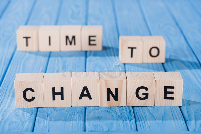close up view of arranged wooden blocks into time to change phrase on blue royalty free stock photography