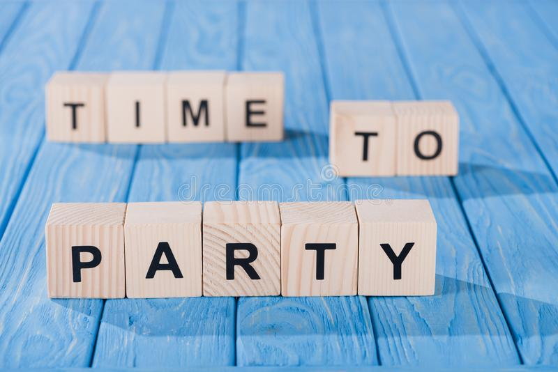 close up view of arranged wooden blocks into time to party phrase on blue stock photo