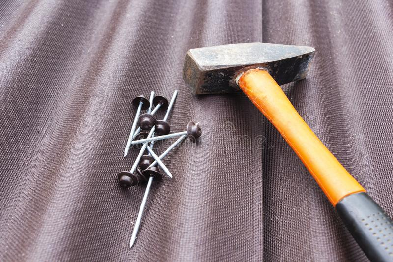Close up view on asphalt roofing shingles background with hammer and nails.  stock image
