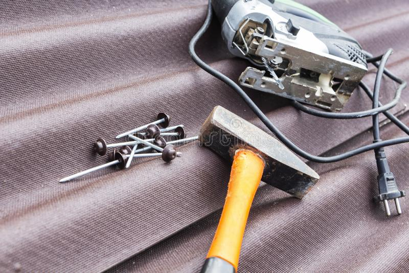 Close up view on asphalt roofing shingles background with hammer and nails.  stock photo