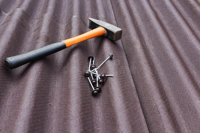 Close up view on asphalt roofing shingles background with hammer and nails.  royalty free stock image