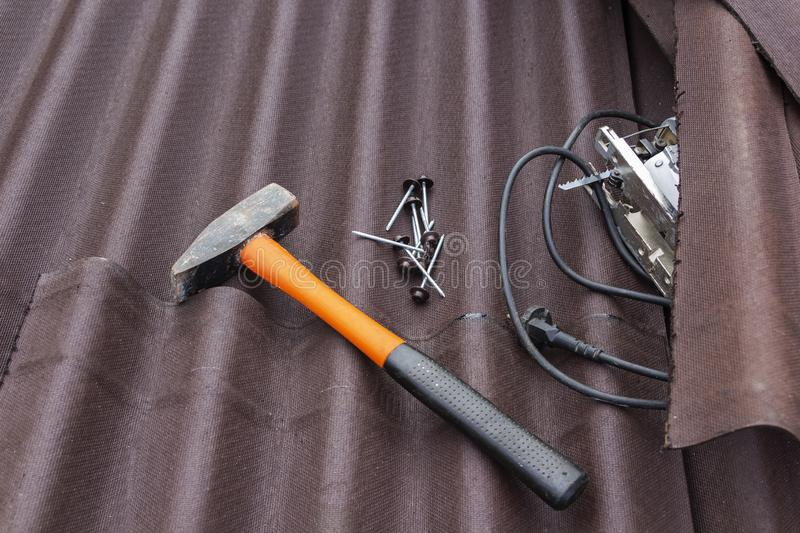Close up view on asphalt roofing shingles background with hammer and nails.  stock images