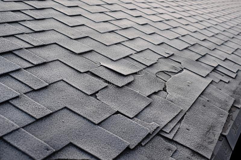 Close up view on Asphalt Roofing Shingles Background. Roof Shingles - Roofing. Shingles roof damage covered with frost. royalty free stock photography