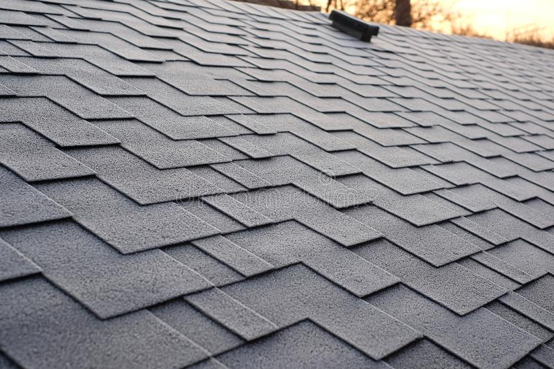 Close up view on Asphalt Roofing Shingles Background. Roof Shingles - Roofing. Shingles roof damage covered with frost. stock photography