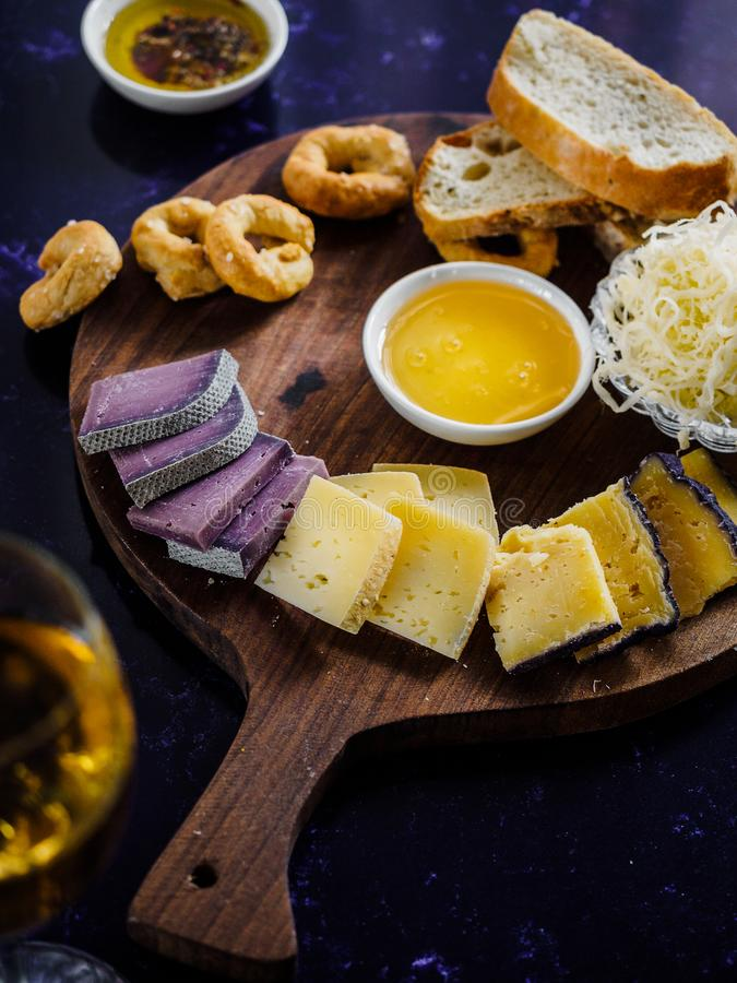 Close up view of assorted cheese types, sauce and bread on wooden. Cutting board royalty free stock photo
