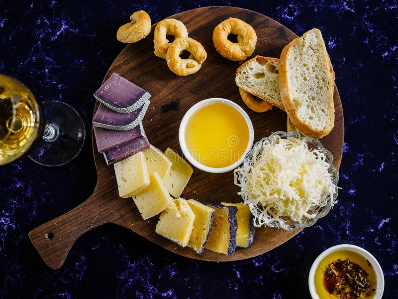 Close up view of assorted cheese types, sauce and bread on wooden. Cutting board stock image