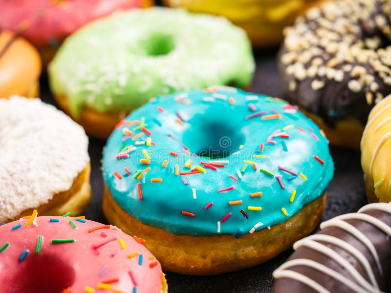 Close up view of assorted colorful donuts. On dark background. Focus on blue glazed doughnut with sprinkles. Shallow DOF stock photography