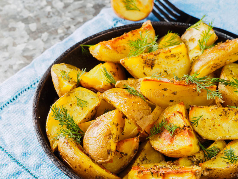 Close up view of backed potatoes in cast iron skillet stock images