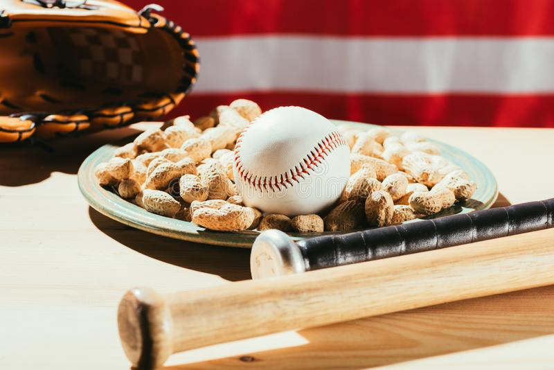 Close-up view of baseball bats, baseball ball on plate with peanuts and leather glove on wooden table with us. Flag behind royalty free stock image