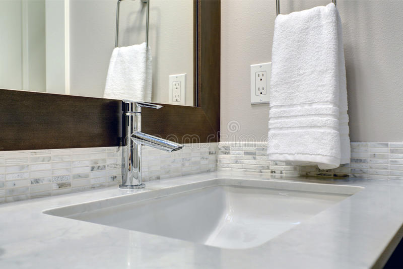 Close-up view of bathroom vanity. Cabinet topped with white and grey counter paired with tile backsplash under framed mirror. Northwest, USA Northwest, USA stock photography