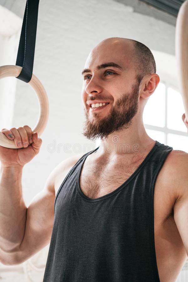 Close up view of bearded fit sportsman holding gymnastic rings at cross gym stock photos
