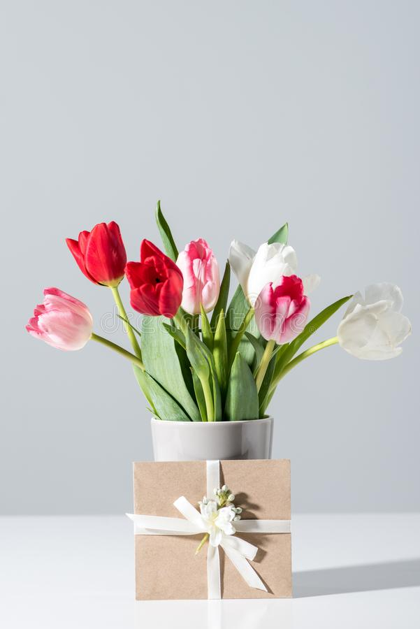 Close-up view of beautiful blooming tulip flowers in vase and envelope royalty free stock image