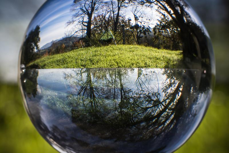 Close up view on beautiful landscape trees in blue sky and green meadow through lens ball sphere, france stock image