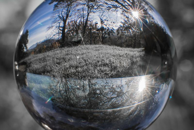 Close up view on beautiful landscape trees in blue sky through lens ball sphere in selective color, france royalty free stock photo